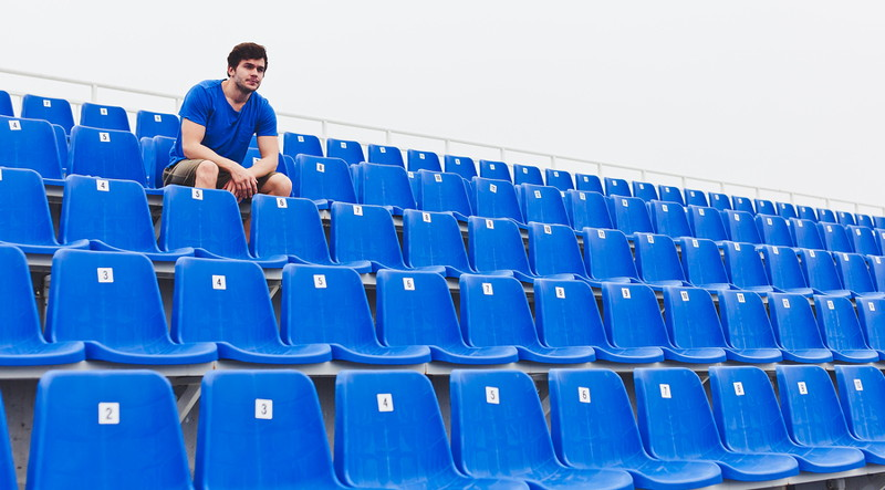 man sat alone in a stadium stand
